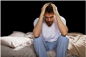 man sitting on bed upset with sleep